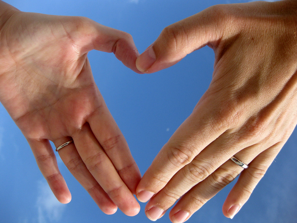 Two left hands forming an outline of a heart shape against a blue sky.