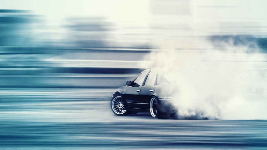 Car doing drifting, and doing a burnout.